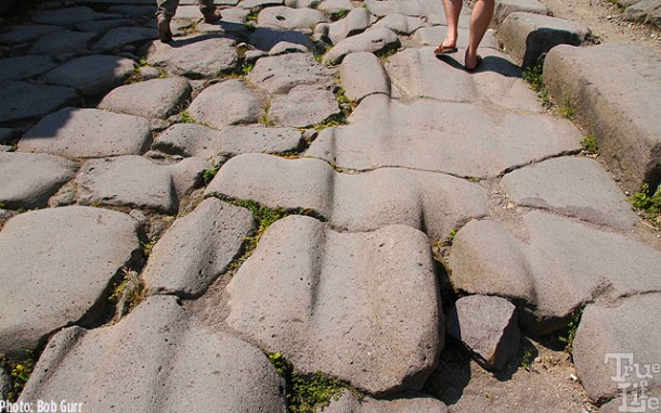 Wagon wheel ruts worn into the street paving stones.