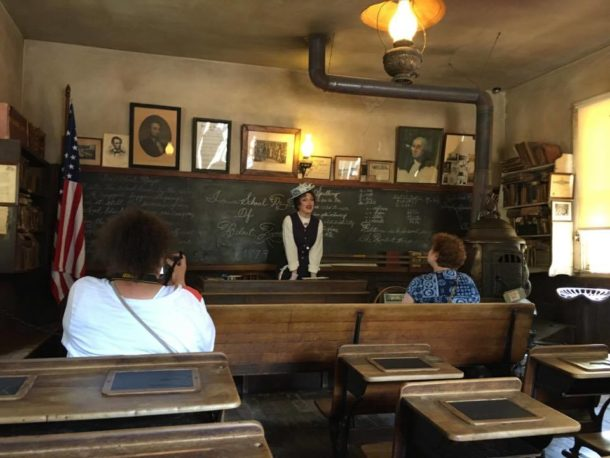 visitors sitting in an old-fashioned classroom while a costumed teacher speaks